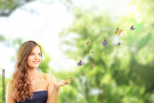 Beautiful female with a butterfly on her hand posing in a park