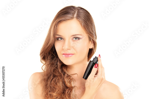 Portrait of a beautiful young female applying a perfume