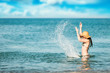 Woman is playing with water splashes at the beach