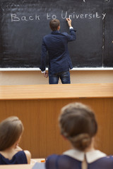 student writing on the chalkboard