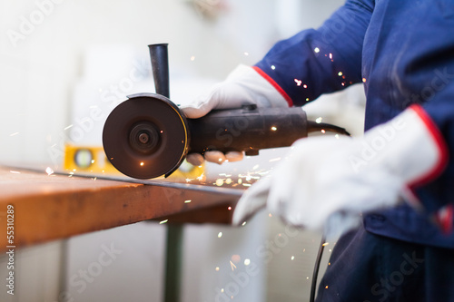 Worker cutting a metal plate