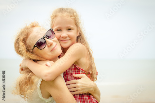 mother and her daughter at the beach