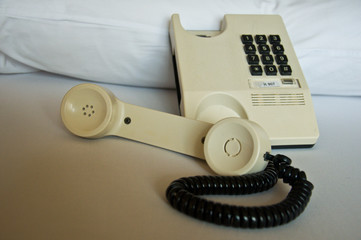 Telephone handset off the hook on bed