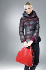 young blonde girl in fur coat with red bag posing