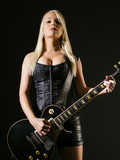 Serious blond female playing electric guitar