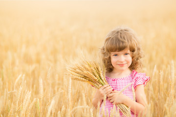 Happy child holding wheat ears