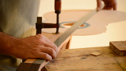 Luthier measures a guitar with a rule