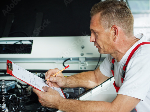 Motor mechanic in front of engine bay checks repair details