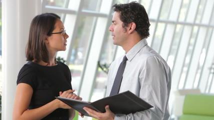 Businessman And Businesswomen Discussing Document