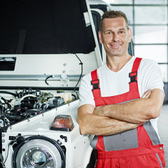 Car mechanic in front of a car in a garage