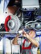 Car mechanic in a garage checks the bracke