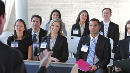 Businesspeople Listening To Speaker At Conference