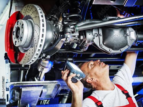 Leinwandbild Motiv Motor mechanic inspecting the engine of a car
