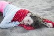 portrait of unhappy little girl  girl lies on the sand.