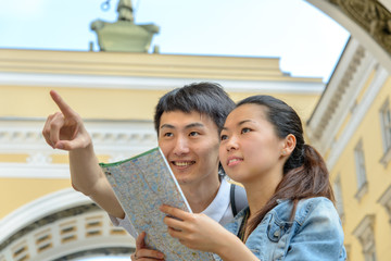 Young tourists studying map