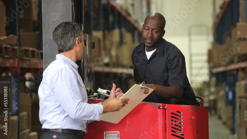 Manager Discussing Paperwork With Fork Lift Driver