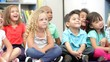 Group Of Elementary Age Schoolchildren Sitting On Floor