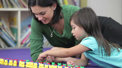 Teacher Showing Girl How To Count With Plastic Toys