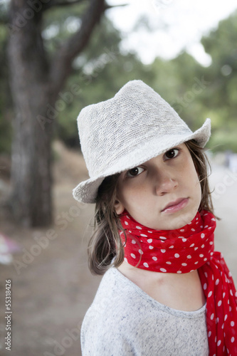 portrait of Unhappy little girl in straw hat