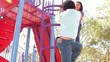 Two Children On Climbing Frame In Park
