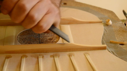 Luthier working with a chisel on a guitar