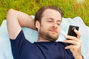 Happy man looking at mobile phone while lying on grass