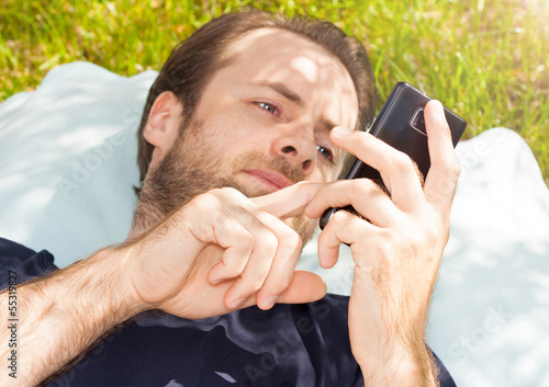 Man looking at mobile phone while lying on grass