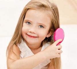 Portrait of smiling little girl brushing her hair