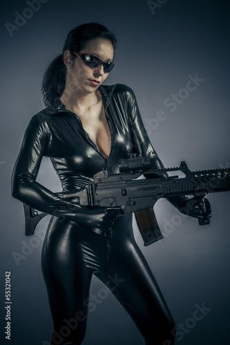 Airsoft guard, police woman holding a big gun, latex costume