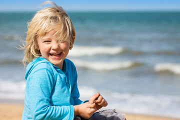 Cute laughing boy at beach
