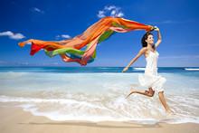 Femme heureuse sautant sur la plage