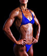 Slim muscled woman against black background