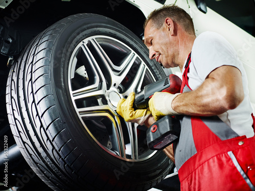 Motor mechanic is changing a tyre with new alu rim
