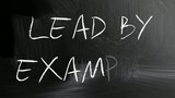 """Lead by example"" handwritten with white chalk on a blackboard"