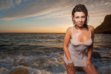 beautiful woman on the beach at sunset wet