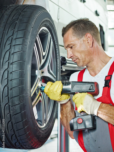 Car mechanic is changing a tyre