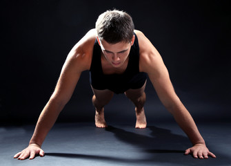 Handsome young muscular sportsman, on dark background