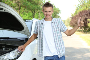 Man on road with car breakdown trying to stop car