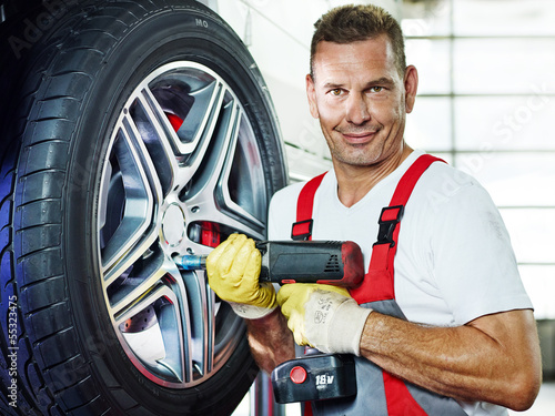 Car mechanic is changing a tyre in a garage