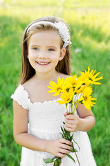 Cute little girl on the meadow with flowers