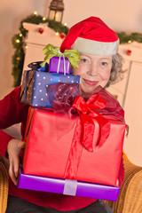 Seniorin mit vielen Geschenken und Weihnachtsmann-Mütze