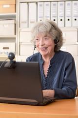 Rentnerin lacht in die Webcam ihres Laptops