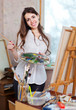 Happy  woman paints on canvas with oil paints