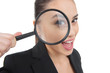 Looking through magnifying glass. Beautiful young woman looking
