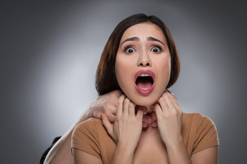 Choking. Portrait of shocked young woman with someones hands cho