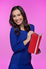 Woman with gift box. Cheerful young woman holding a gift box and