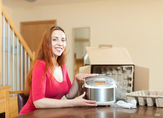 Young woman with electric slow cooker at home