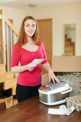 Cute young  housewife in red unpacking new multicooker in home