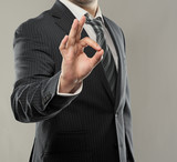 Young successful businessman showing ok symbol