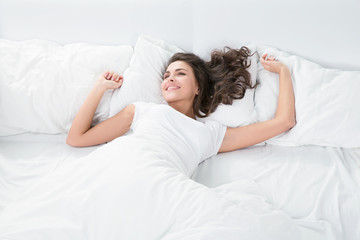 young woman lying on the white linen in bed
